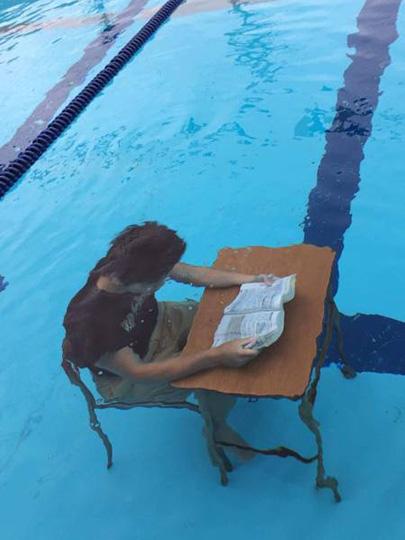 물속에서 책 읽는 남성