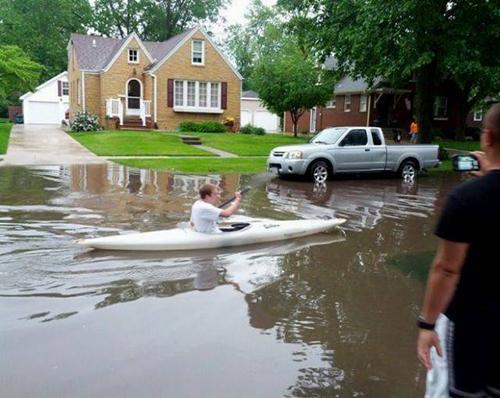 홍수 속에서 카누를 타는 남성